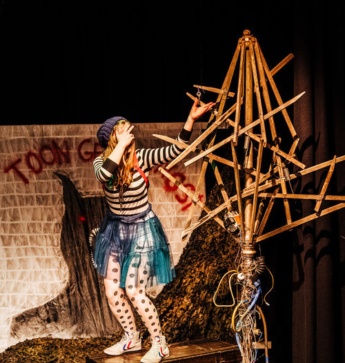 Jolien staat angstig op een grote kist. In een grote houten boom hangen oude sleutels. Haar hand reikt naar één van de sleutels.