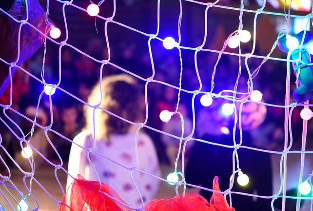 Schaduwen van spelers en publiek achter een gordijn van lichtjes.