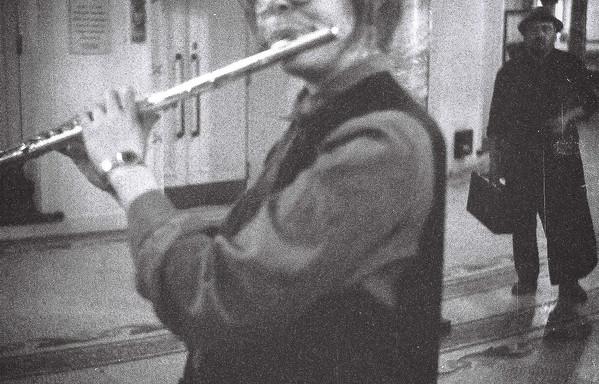 Sandra speelt fluit. Oskar de verteller staat te wachten op de achtergrond.