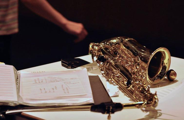 Tafel met script, partituren, een gsm en een saxofoon.