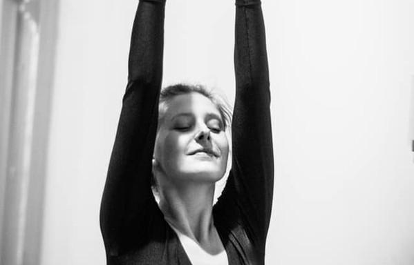 Sarah danst met haar armen hoog in de lucht.