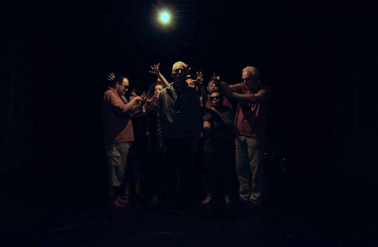 De groep staat onder een lamp. Koen staat op de voorgrond en zegt zijn tekst. Hij is omringt door de handen van de andere spelers.