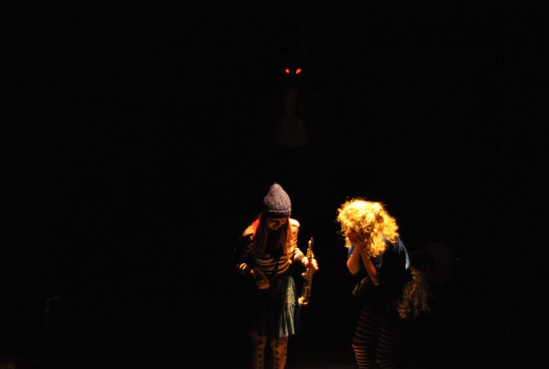 Spot op Jolien en Sarah. Achter hen duiken twee rode ogen op uit het duister.