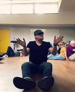 Filip Van Zomeren: Beeld Filip tijdens repetitie Toen De Goden Sliepen. Filip zit voor de groep en vertelt met ondersteunende handgebaren een verhalen.