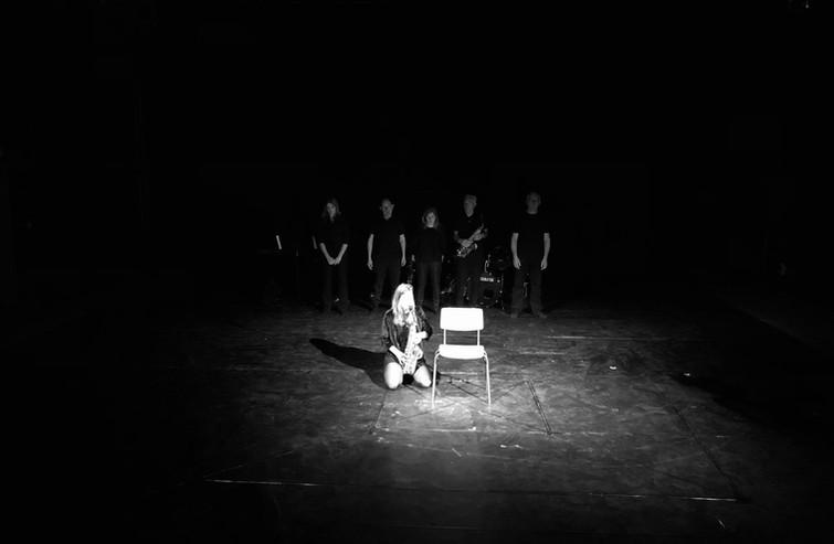 Jolien speelt saxofoon naast een lege stoel. Alle spelers staan op een rij op de achtergrond.