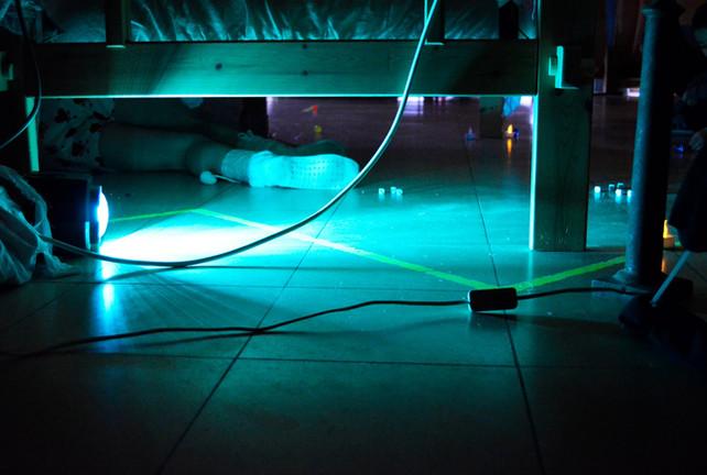 Sfeerbeeld: Een ijl, blauw licht. Een voet verdwijnt onder een bed.