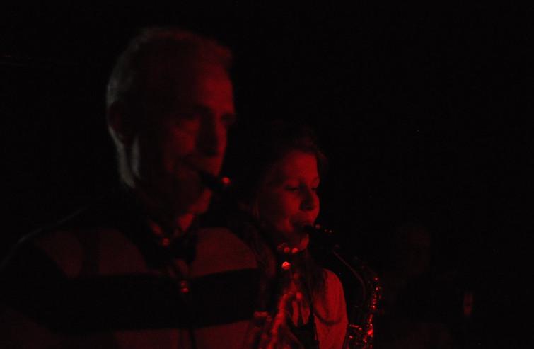 Koen en Jolien spelen saxofoon in een rood licht.
