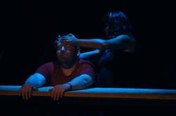 Een man licht op een grote tafel. Een meisje danst om hem heen en richt zijn hoofd op.