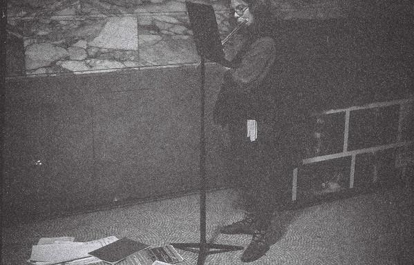 Sandra speelt fluit. Voor haar liggen allemaal partituren verspreid op de grond.