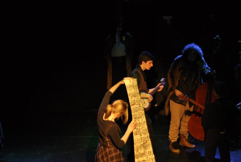 De band speelt muziek op de achtergrond. Op de voorgrond vindt Esther een enorme, magische partituur.
