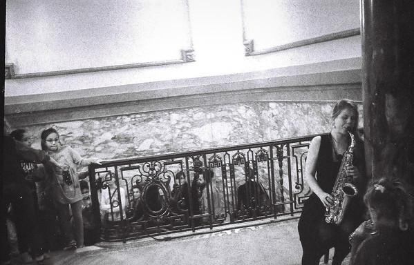 Jolien speelt saxofoon tegen een zuil. Het publiek ontdekt haar.
