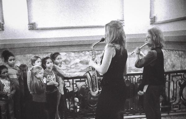 Kinderen kijken geboeid naar fluitiste Sandra en saxofoniste Jolien.