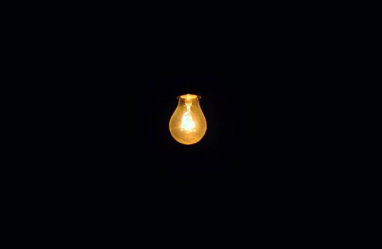 Een lampje hangt aan het plafond in een verduisterde zaal.
