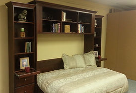Murphy bed with upper cabinets shown open.