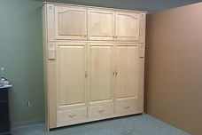 A murphy wall bed turned sideways with raised panel front  and upper bookcase.