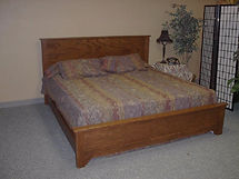 An oak bed with a panel headboard