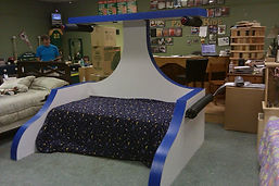 A kids bed that looks like a star fighter