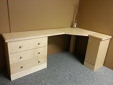 A corner desk in maple wood