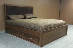 A dark stained platform bed