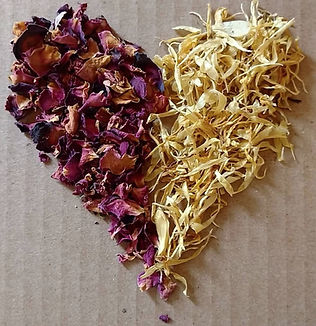 a heart shape on a brown paper background - formed from 2 types of petals - roses and calendula