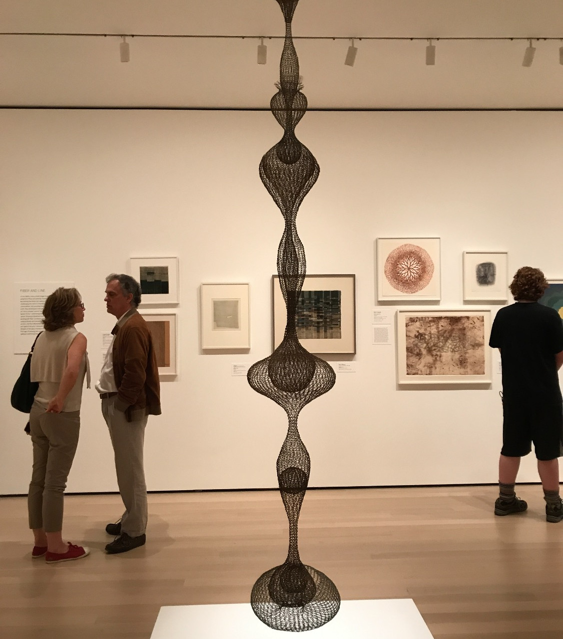 People looking around the exhibit in front of a Ruth Asawa sculpture
