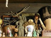 Photographie de l'atelier de Lucie de Syracuse représentant une poupée, une tête d'ours, un chat et un lapin