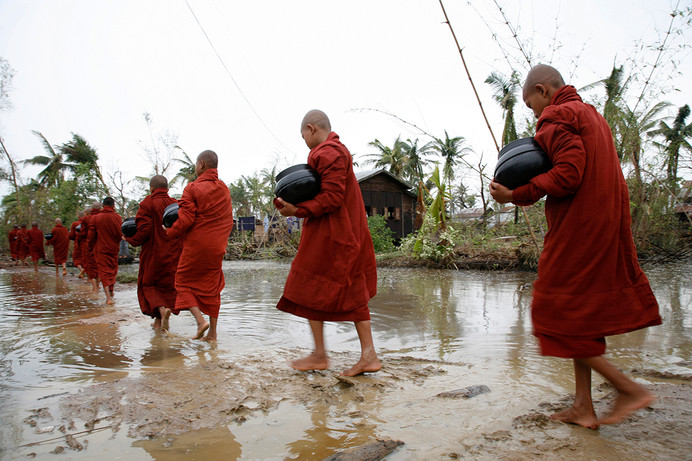 Monks walk in a procession to collect alms from residents at Kawmuu town affected by Cyclone Nargis in Yangon Division of Myanmar (Burma).