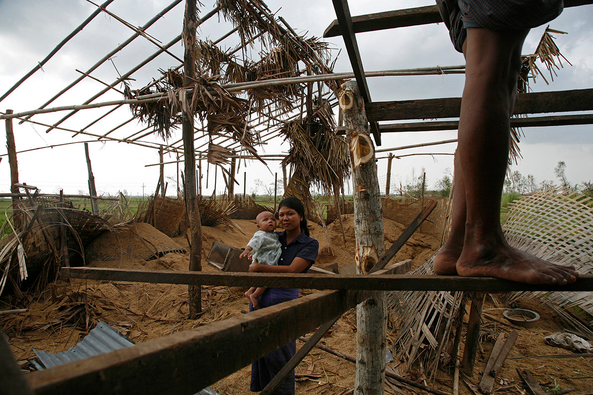 A young mother and her child, watches a family member as he repairs the roof of their rice mill and home damaged by Cyclone Nargis at Thar Yar Wae village, on the road to Bogalay, in the Irrawaddy Division of Myanmar (Burma).