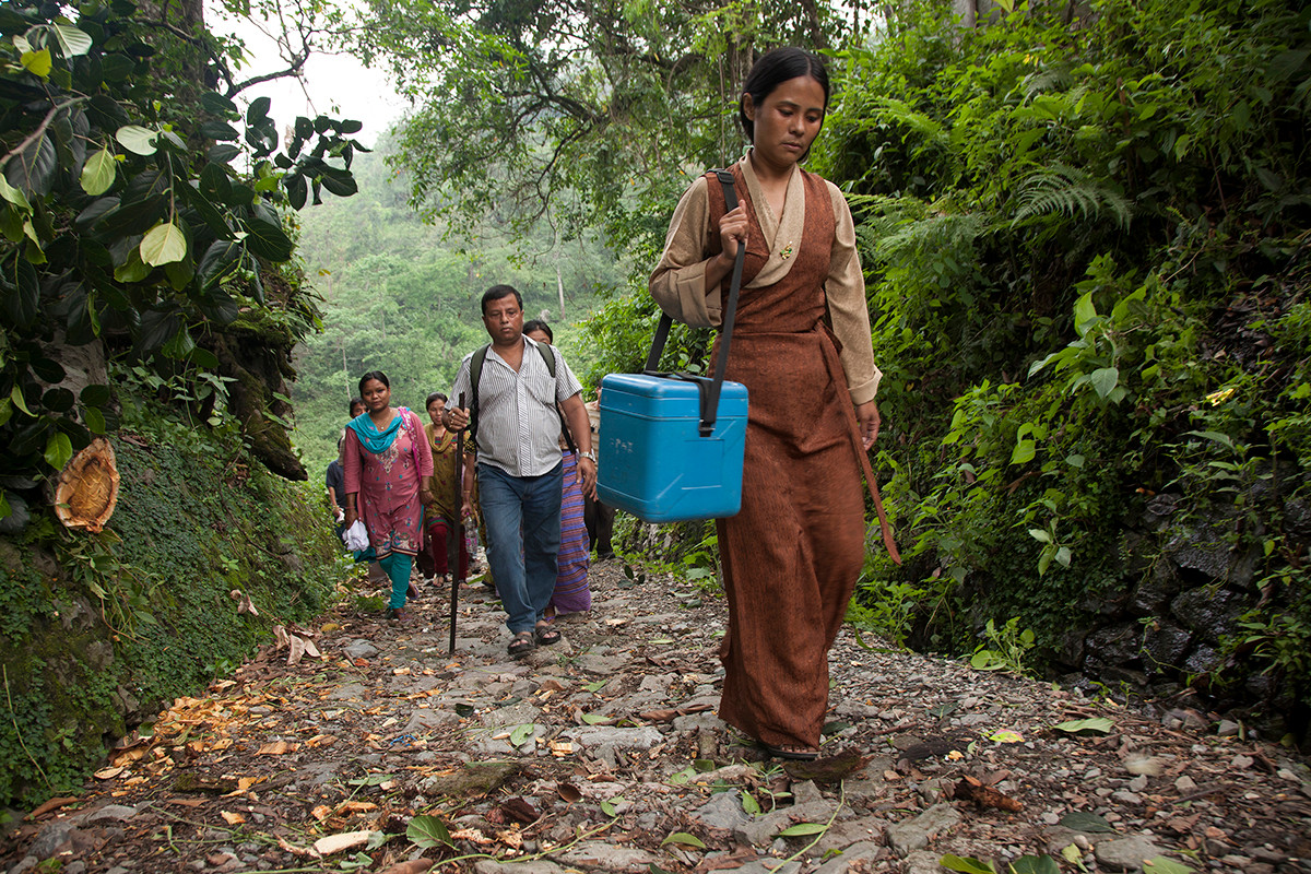 Family Planning Association of India's (FPAI) Kalchini branch staff trek through forests to conduct an immunization camp in the Buxa Hills, Kalchini, West Bengal, India, 2012.