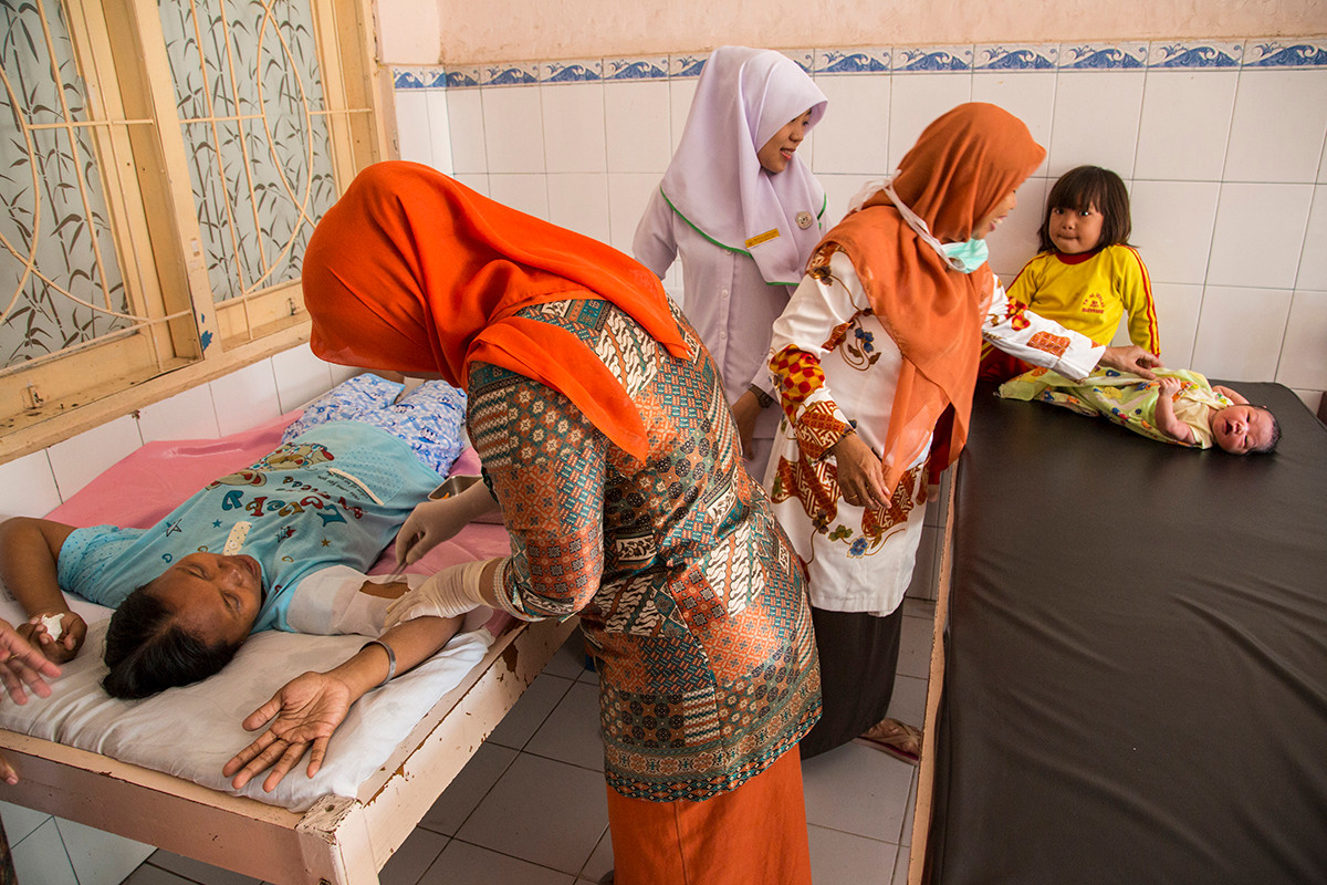 Ibu Siti Hani, who just delivered her 5th child, a baby girl, the day before, has an implant inserted at Puskemas Bara-baraay in Makassar, Indonesia, 2015.