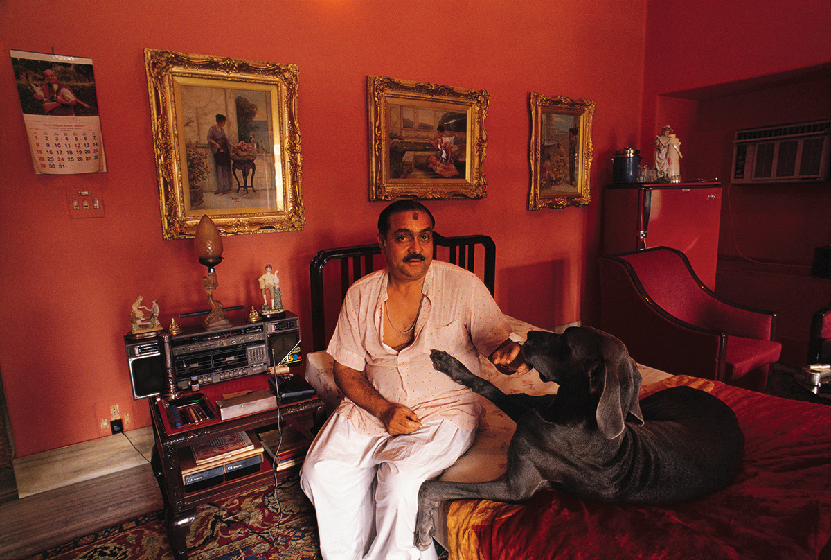 Bikaner, Rajasthan. 1990: Maharaja Narendra Singh Rathore in the bedroom of his bungalow with his Great Dane bitches. Estranged from his family, the reclusive Maharaja Narendra Singh lived away from the palace, surrounding his world in the colour red and his menagerie of animals till his death in 2003.