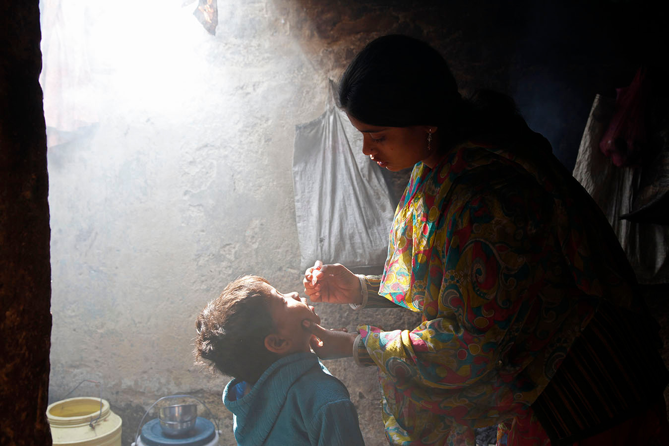 House-to-house polio vaccination team member gives a child polio vaccine drops in a home in the Kamla Nehru Nagar slum in Patna, Bihar, India, 2010.