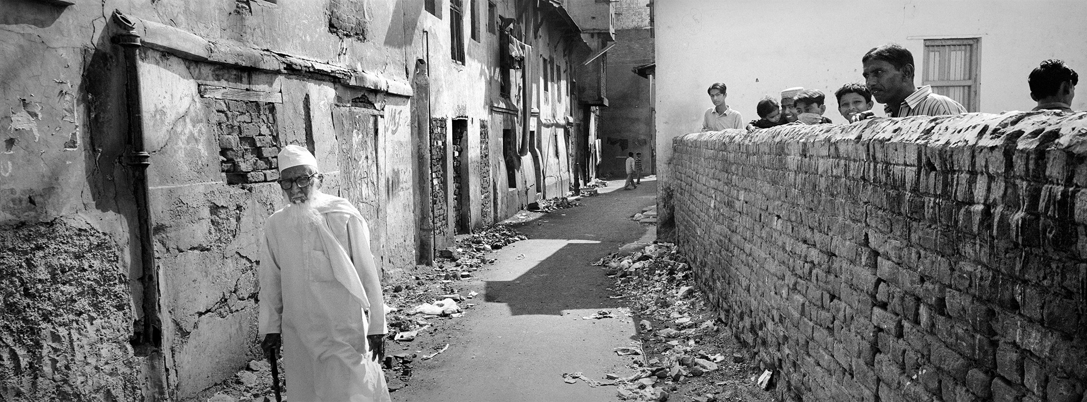 Muslim residents watch as an old man walks past the Wall in Jilaiwada.