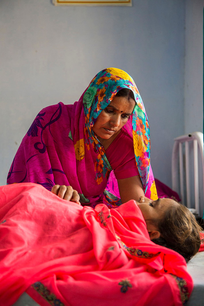 Anganwadi worker, Sushila Sharma comforts Meera Bawa who is recovering after laproscopy at the Marie Stopes India outreach clinic at the government primary health centre in Chandlai village, near Jaipur, Rajasthan, India, 2015.