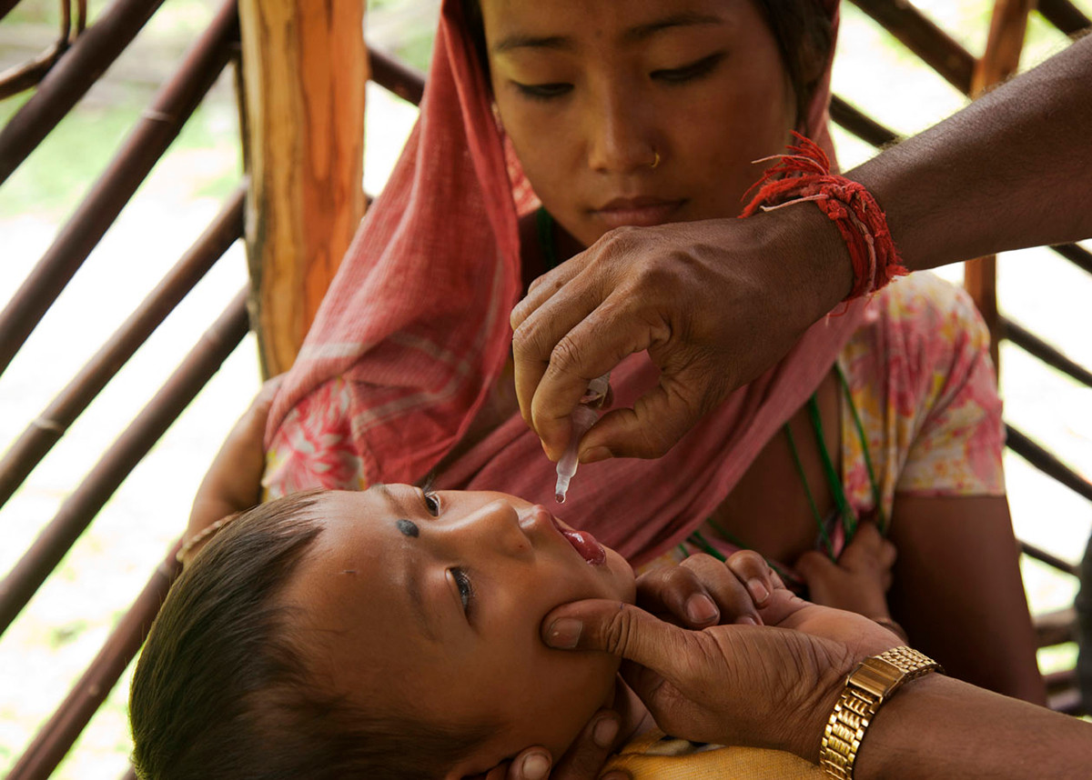 A child received oral polio vaccine at an immunization camp conducted by Family Planning Association of India's (FPAI) Kalchini branch at Buxa Fort, Kalchini, West Bengal, India, 2012.
