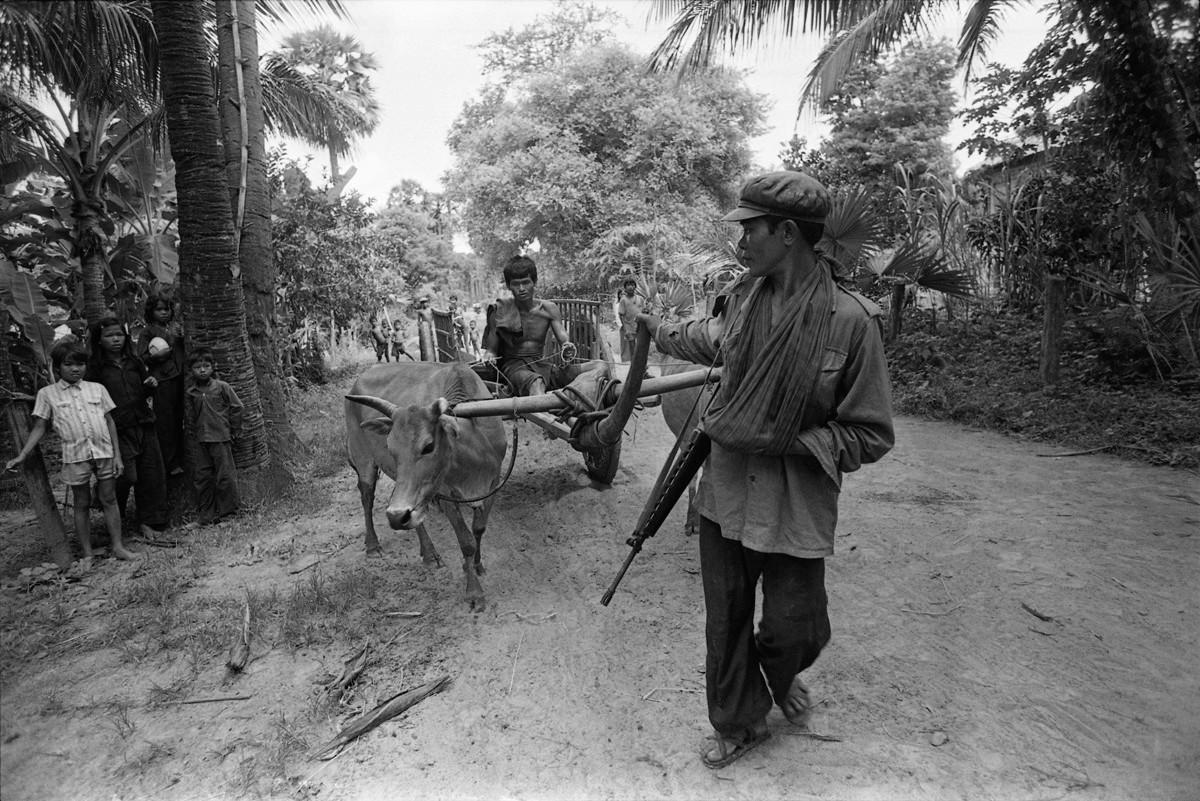 A militiaman assists a bullock cart driver at Dong Russey village in Kompong Chnang province.
