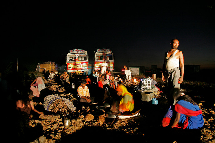 Ahmednagar district, Maharashtra, 2007: Seasonal migrant labour on their way to a sugar factory in trucks camp out at night during their journey.
