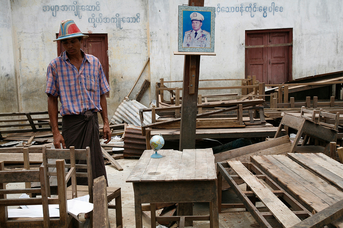 A resident stands beside a portrait of General Than Shwe in a school destroyed by Cyclone Nargis in a village near Kaw Hmu, in the Yangon Division of Myanmar (Burma).