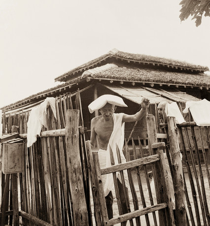 Sevagram Ashram, 1940: Mahatma Gandhi in front of his office hut, carrying a pillow on his head as protection against severe heat.