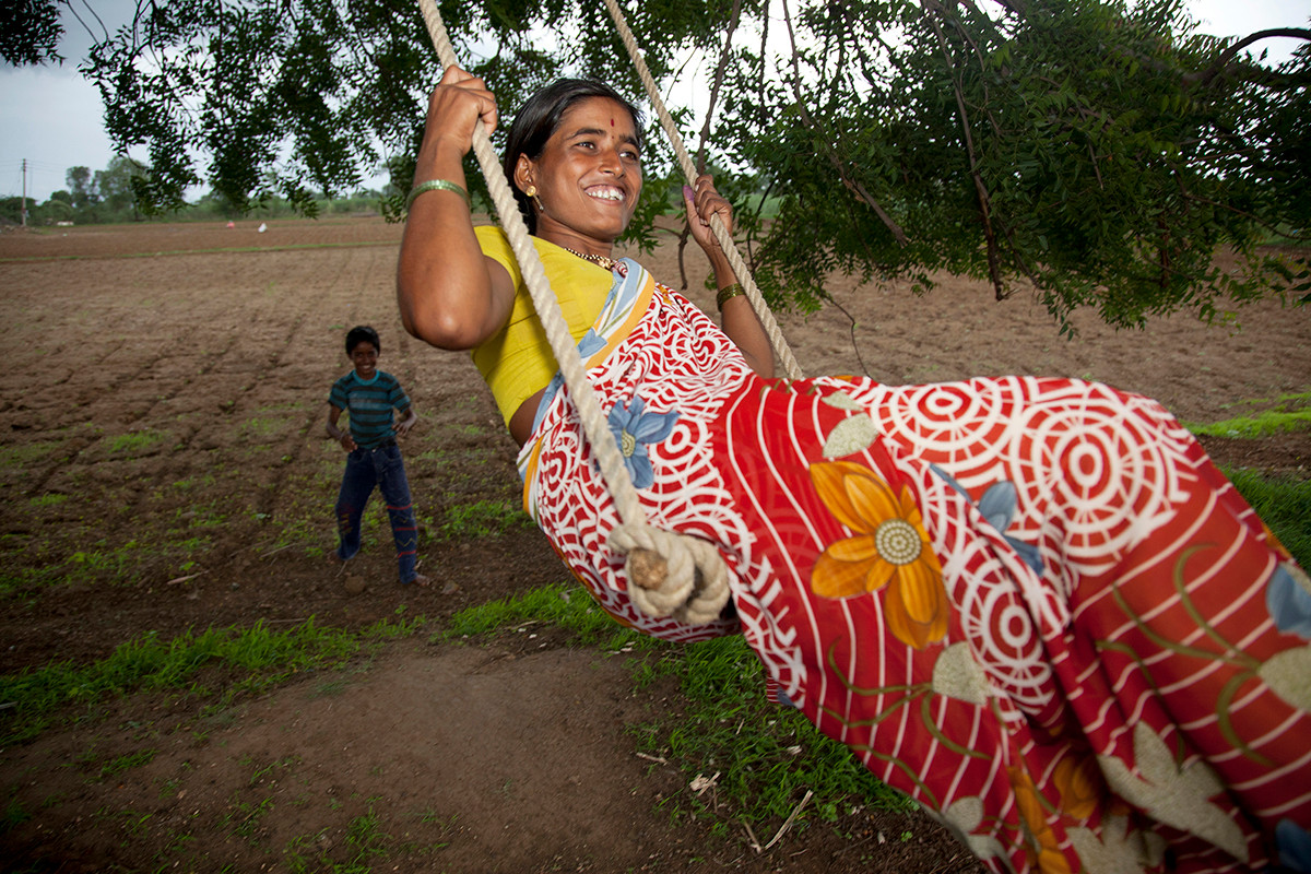 Chandrakala More, a member of the Shevgaon Block PLHIV Support Group, under the Ahmednagar district NMP+ (Network of Maharshtra by People Living with HIV-AIDS), with her son at her farm in Balamtakli village, Ahmednagar district, Maharashtra, India, 2011.