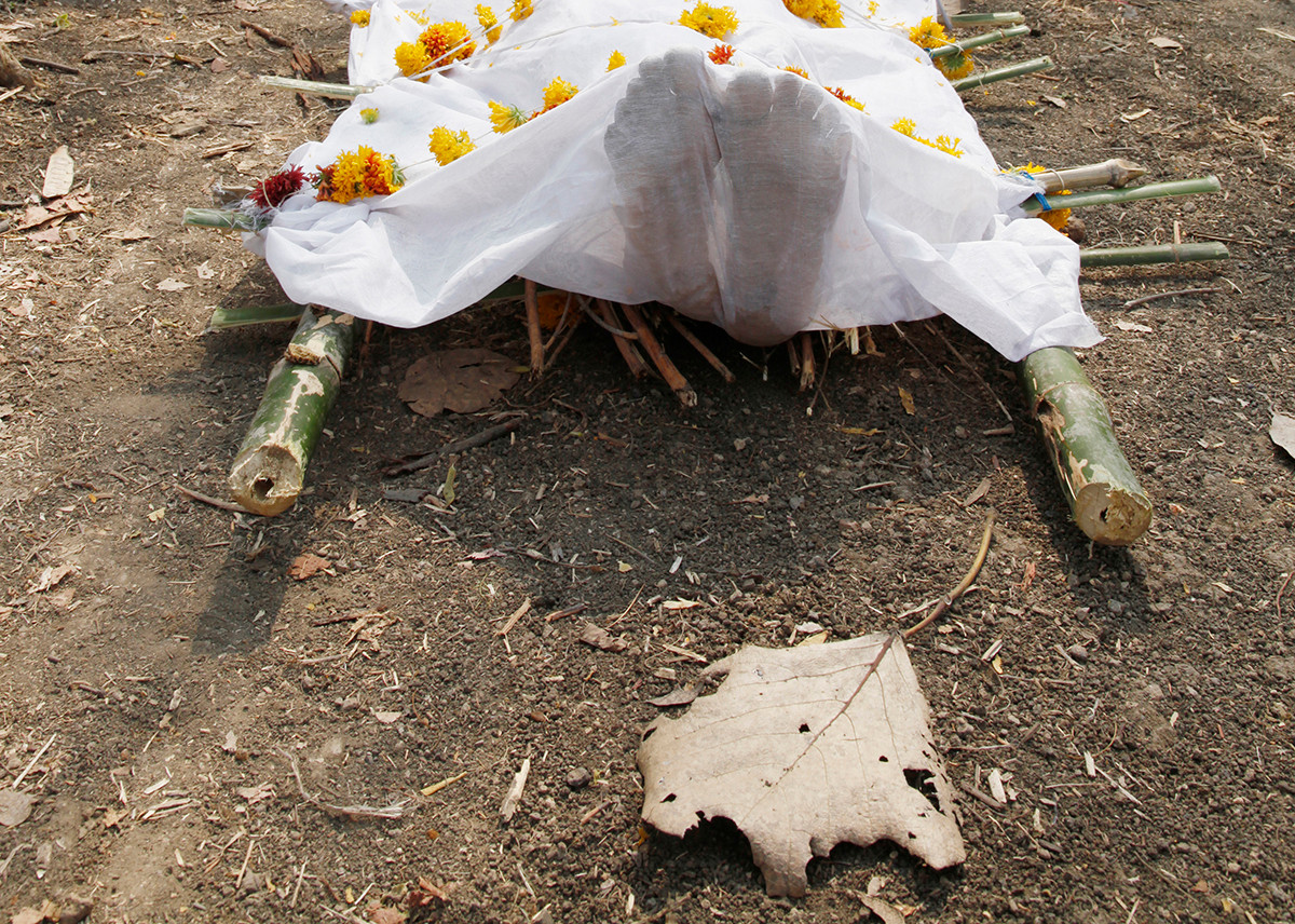 The body of Vijay Thamke, a farmer from Sonbardi village who committed suicide, lies on the ground as his funeral pyre is prepared nearby.
