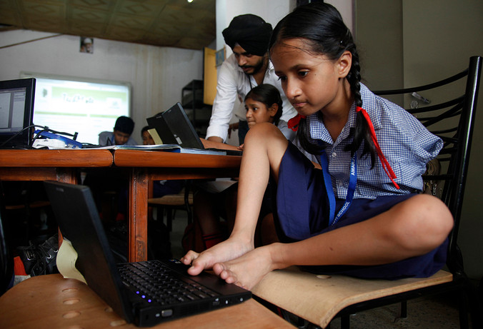Nishta, a differently abled student, uses her toes to operate a notebook in an AIF DE Dell connected classroom at Amar Jyoti Charitable Trust school at Kakardooma, Delhi, India, 2013.