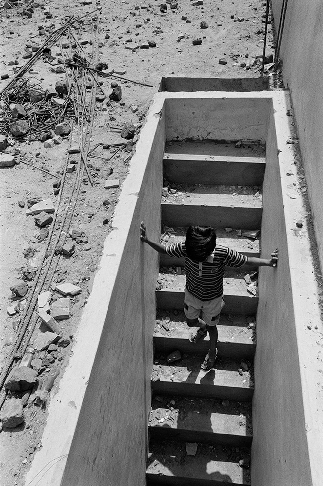 A Hindu boy climbs down from the roof of a temple littered with debris from the riot in Vanmadi Vanka Ni Pol.