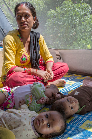 A beneficiary and babies at a Female Friendly Space for distribution of Dignity Kits at Bungamati, Kathmandu, Nepal, 2015.