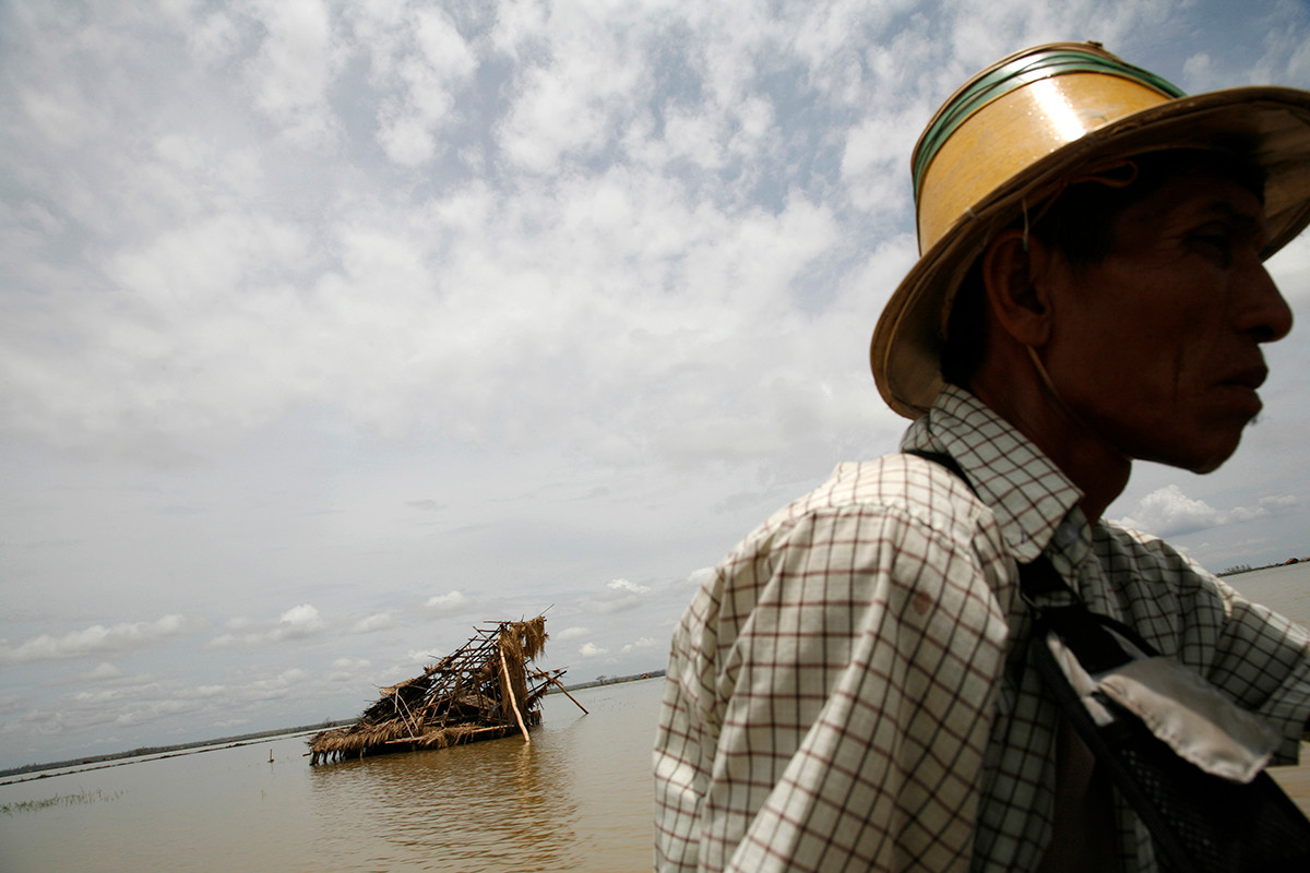 A  home destroyed by Cyclone Nargis  is seen behind a boatman in a village near Kaw Hmu, in the Yangon Division of Myanmar (Burma).