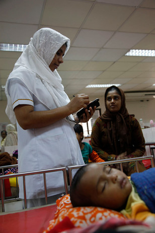 A nursisng assistant uses a electronic hand-held device to record observations of a patient at ICDDR,B Dhaka Hospital, Bangladesh, 2012.
