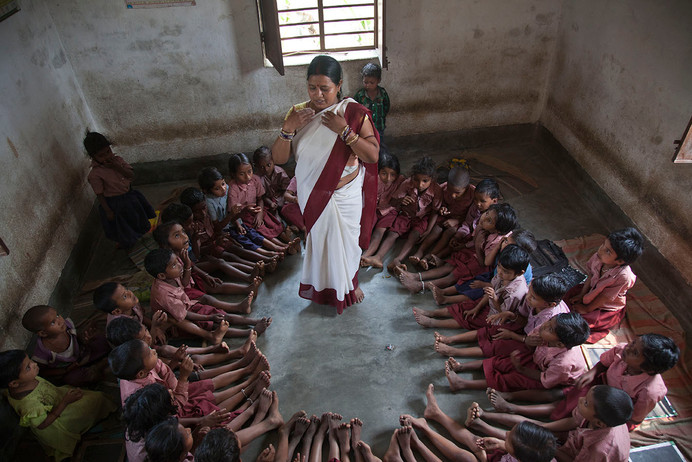 Anganwadi worker, Manju Kumari teaches her wards through a play session at her Anganwadi Centre in Samda village, Saharsa district, Bihar, India, 2013.