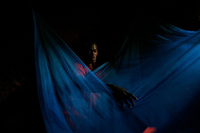 Village health worker, Mohammed, inspects a bed-net at the home of Amina Waziri in Songa village, Muheza, Tanzania, 2007.