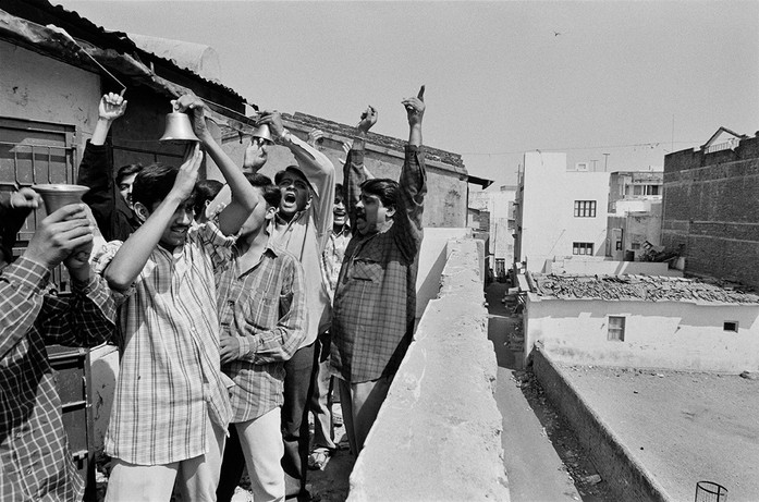 Hindu youths from Vanmadi Vanka Ni Pol shout slogans from the roof of one of the homes on the Wall overlooking the Muslim neighbourhood of Jilaiwada.