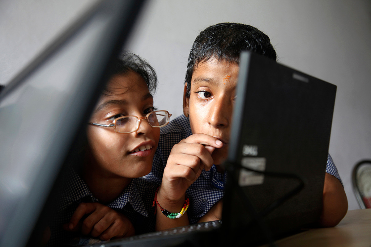 Differently abled students Harshit (right) and Muskaan (centre) in the AIF DE Dell connected classroom at Amar Jyoti Charitable Trust school at Kakardooma, Delhi, India, 2013.